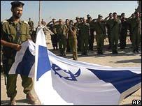 Солдаты сворачивают флаг в Кфар-дароме