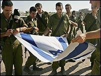 Israeli soldiers fold national flag in Gaza