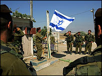 Israeli soldiers lower flag at Yareach outpost, southern Gaza Strip