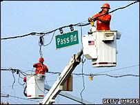 Dos hombres reparando cables de electricidad