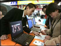 A Lenovo salesman demonstrates an IBM laptop