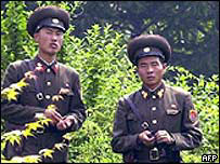 North Korean soldiers look to the South from the northern side of the border zone