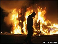A man walks past a burning vehicle