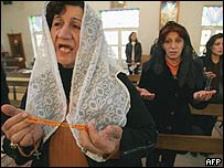 Catholic women pray during a mass, west of Baghdad