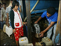 Residents in Jakarta queue up for kerosene at a distribution point