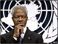 Kofi Annan stands in front of the UN logo