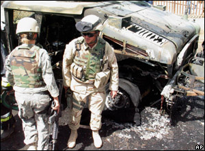 US soldiers near wrecked vehicle after a bomb exploded near a military convoy.