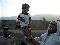 Village father with child as dusk falls over Shomali plain