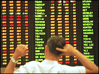 A man looks at an electric screen showing share prices