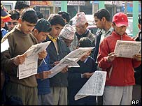 Nepalese people read newspapers at a roadside in Kathmandu