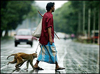 Man in Kolkata, India, makes his living with performing monkeys