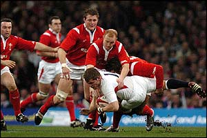 Mark Cueto is held by Wales players