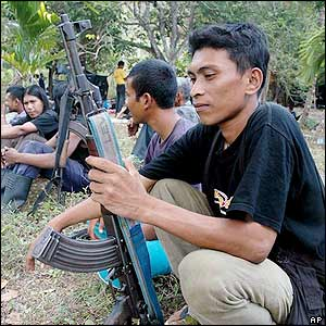 A member of the Free Aceh Movement (GAM) holds his rifle to be collected and handed over to international monitors later this week in Bireun, Aceh province, Indonesia Tuesday Sept. 13, 2005