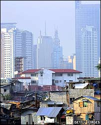 Shacks stacked on top of each other stand out from the financial district of Makati skyline along the polluted Maricaban River in the slums on 9 July 2005