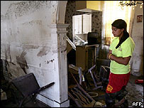 Emily Martinez inspects her flood-damaged home in New Orleans