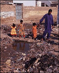 Karachi - children crossing over the sewage flow - credit WaterAid/Caroline Penn