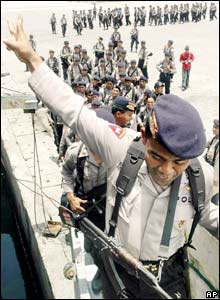An Indonesian policeman waves as he boards a ship to leave Aceh,  Wednesday September 14, in Lhokseumawe, Aceh