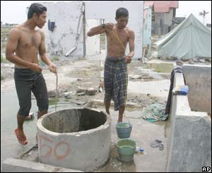 Two Acehnese men take a bucket shower near their makeshift home in Banda Aceh, September 8, 2005.
