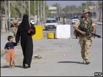جندي بريطاني خلال دورية يسير غلى جانب امرأة عراقية تصطحب طفلها في البصرة