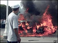 A man looks at a car burning in Andijan, Uzbekistan