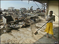 Jakfar, aged 41, cleans up debris from his damaged house in Keudah village, Banda Aceh, 7 Feb