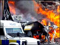 Burning lorry and police Land Rover