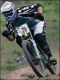 A downhill mountain biker hurtles down a hill