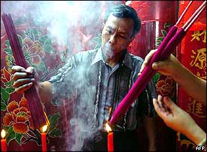Indonesian Chinese light joss-sticks at a Buddhist temple during the Lunar New Year eve in Jakarta 08 February 2005.