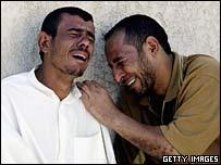 Iraqi men cry outside the al-Kadhimiyah hospital morgue