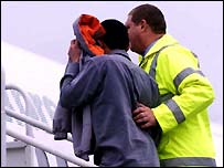 Asylum seeker escorted onto a plane