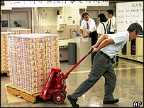 Man pulling trolley stacked with yen banknotes