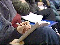 Student writing in lecture hall