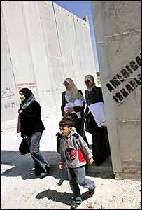 Palestinian women and children pass through the separation barrier built by Israel in Bethlehem
