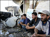 Iraqi men gather at the site of a suicide attack in Tuz Khurmatu