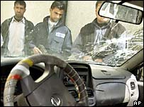 Iraqi police examine the car in which Abdul Hussein Khazal and his son were killed