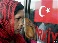 An Indonesian woman, holding bread which she has received from a Turkish relief agency looks through the front window of the headquarters of the Turkish relief effort in Banda Aceh, 9 Feb