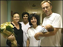 The happy parents with two of the hospital staff