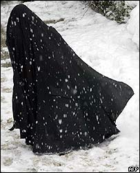 An Iranian woman in a chador makes her way through the snow