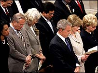 President George W Bush bows his head in prayer at the National Cathedral