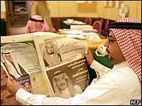 A Saudi man reads a newspaper with pictures of municipal election candidates in Riyadh