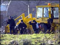 Officers at scene of search with a digger