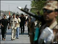 Shia Muslims walk towards the Iraqi city of Karbala as a soldier stands guard, 18 September 2005