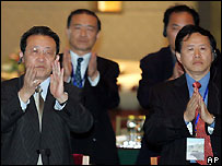 North Korean delegates applaud at the close of the talks over North Korea's nuclear crisis in Beijing, September 19, 2005.