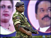 Sri Lankan soldier near party poster in Sri Lanka
