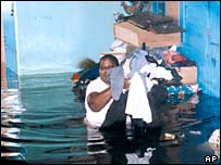 A Georgetown woman carries clothes from her flooded home