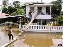 A Guyanese family use a makeshift bridge outside their flooded home in Georgetown