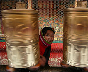 Mujer junto a ruedas de oraci�n en Jokhang, Lhasa.