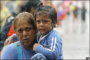 Una mujer llega al aeropuerto de La Guaira con su hija luego de ser rescatad.