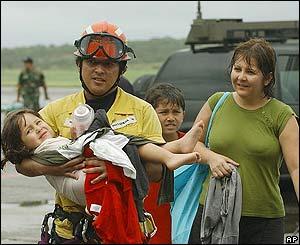 Un paramédico llega con una niña y su familia al aeropuerto de Maiquetía, luego de rescatarlas de una playa.