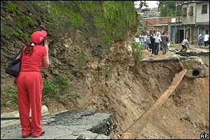 Una mujer grita a sus vecinos a través de una vía derrumbada, en Fenis, en Caracas,